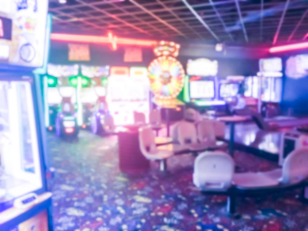 Vintage blurred motion game room at entertainment complex in Dallas, Texas, USA. Abstract arcade area background.