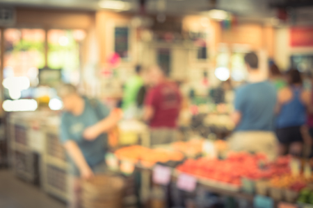 Blurred image line of customers at check-out counter grocery in USA. Concept of busy shoppers waiting at local farmer market. Business concept, bokeh light