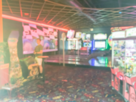 Motion blurred game room at entertainment complex in America. Abstract blurry arcade area with players. Imagens