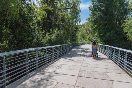 Back view Asian woman pushing stroller along boardwalk in downto