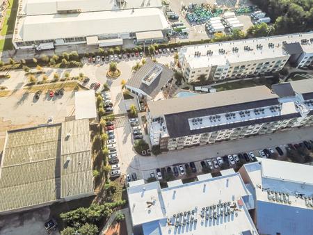 Aerial view new condominium building near large warehouse