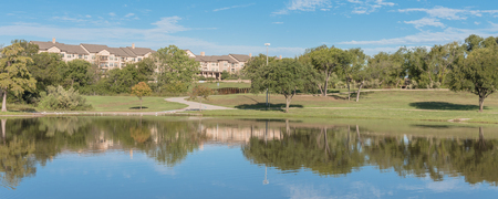 Panoramic urban park with lake reflection and apartment complex in background near Dallas