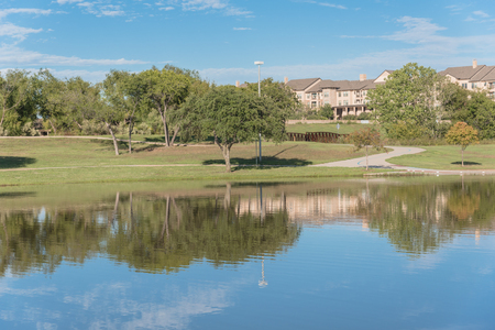 Beautiful urban park with lake reflection and apartment complex in background near Dallas
