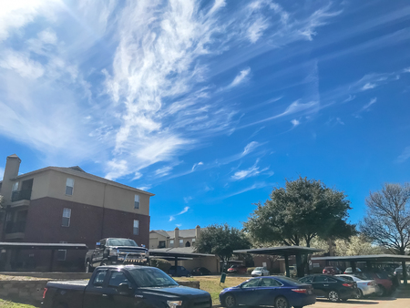 New apartment complex with covered parking under sunny cloud sky in Texas