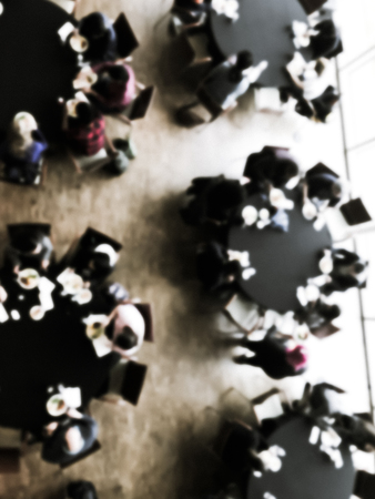 Vintage tone blurred top view lunch break at conference meeting. Defocused delegates networking on round banquet tables, catering food buffet. Diverse group participants on business, entrepreneurship