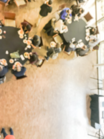 Blurred motion top view lunch break at conference meeting. Defocused delegates networking on round banquet tables, catering food buffet. Diverse group of participants on business, entrepreneurship