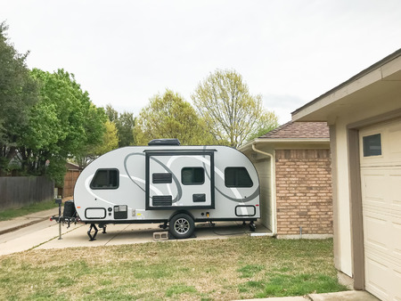 RV trailer parked at backyard of single family house, side view