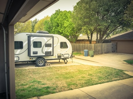 RV trailer parked at backyard of single family house