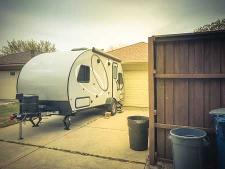 RV trailer parked at backyard of single family house, rear view