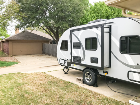 Side view of RV trailer parked at house garage backyard