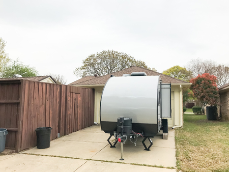 Rear view of RV trailer parked at house garage backyard
