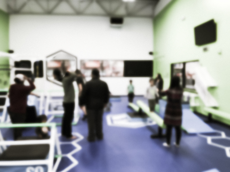 Blurry background parent and children playing at gym class in USA
