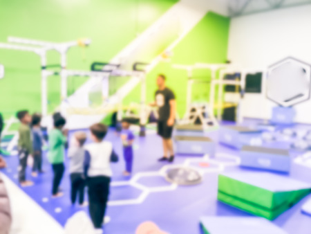 Blurry background coach and kids at children gym class in USA Stock Photo