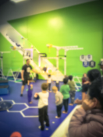 Blurry background parent watching children playing at gym in USA Stock Photo