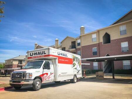 LEWISVILLE, TX, USA-APR 5, 2019: U-Haul truck and boxes at apartment complex. Loading ramp, dolly waiting to transport. American moving equipment and storage rental company, based in Phoenix, Arizona