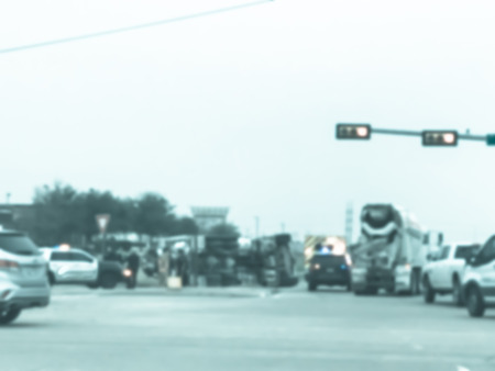 Vintage tone blurred abstract dramatic car accident at street intersection near traffic lights with big semi truck rollover. Police cars, fire truck and crew rescue injured people near Dallas, Texas