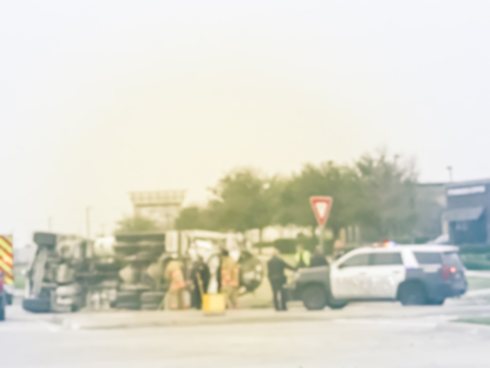 Blurred abstract dramatic car accident at street intersection near traffic lights with big semi truck rollover. Police cars, fire truck and crew rescue injured people near Dallas, Texas, USA