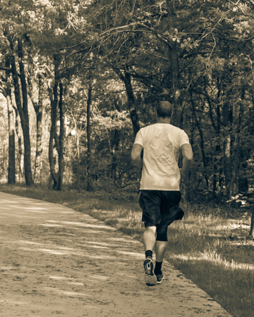 Vintage tone rear view of senior Caucasian man running at nature park during sunset. Healthy person in white crew shirt and long sock running on concrete pathway in natural area in Texas, USA Imagens