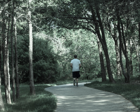 Senior Caucasian man running at nature park during sunset. Rear view of healthy person in white crew shirt and long sock running on s-curved concrete pathway in natural area near Dallas, Texas, USA Imagens