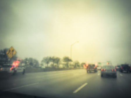 Blurred motion road accident on wet rainy day near Dallas, Texas, USA. Fire trucks and police car support and rescue injured people. Bad driving condition and severe weather concept