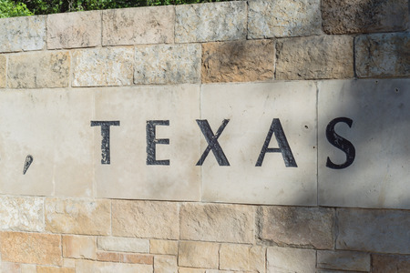 Old stone texture of Texas with a comma word on wall brick