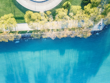 Aerial view Milton Lee Olive Park waterfront in Chicago with multiple fountains creating large, circular seating areas. Beautiful turquoise water from Lake Michigan