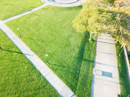 Top view of Milton Lee Olive Park waterfront in Chicago with multiple fountains creating large, circular seating areas. Beautiful green grass lawn in early morning warm light
