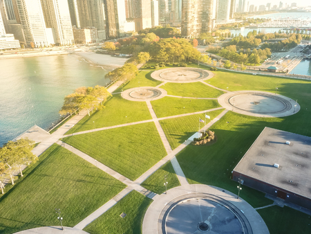 Bird eye view of waterfront Milton Lee Olive Park with Chicago skylines in early morning light. Multiple fountains creating large, circular seating areas. Beautiful turquoise water from Lake Michigan