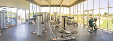 Panoramic blurry background open fitness center with people workout at new home community