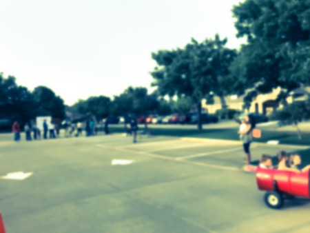 Filtered tone blurry background fun wagon train ride for kids and parents at school event