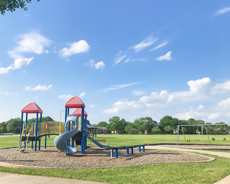 Public playground for kids at green park on sunny day in Texas, USA