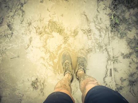 Top view man wearing sport shoes sneakers on muddy race track