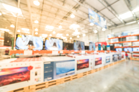 Blurry background row of modern TVs at electronic department of wholesale store