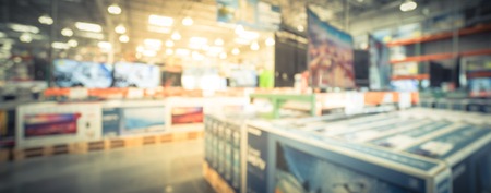 Panoramic blurry background row of modern TVs at electronic department of wholesale store
