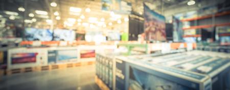 Panoramische verschwommene Hintergrundreihe moderner Fernseher in der elektronischen Abteilung des Großhandelsgeschäfts