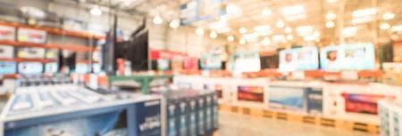 Panoramische verschwommene Hintergrundreihe moderner Fernseher in der elektronischen Abteilung des Großhandelsgeschäfts Standard-Bild