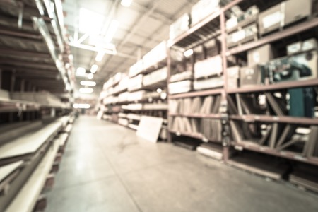 Filtered image blurry background lumber stacks on shelves at American hardware store Stock Photo