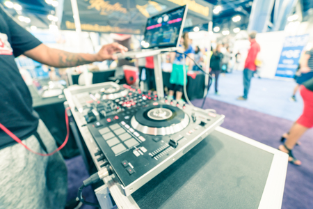 Blurry background tattoo hand of DJ mixing music on laptop at event expo Standard-Bild - 123152867