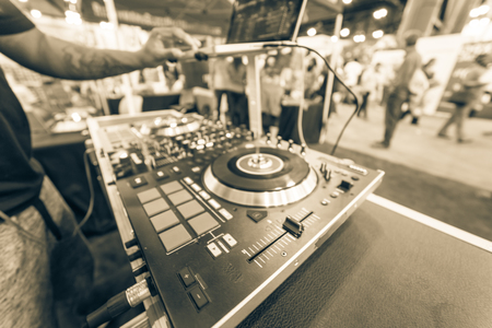 Blurry background tattoo hand of DJ mixing music on laptop at event expo Standard-Bild - 123152946