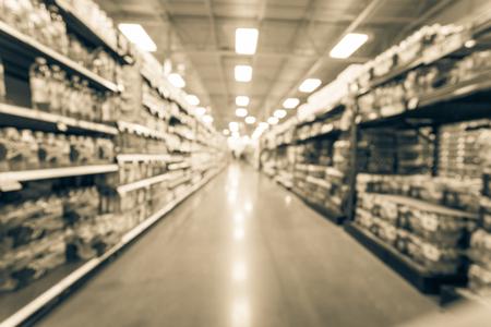 Imagen filtrada fondo borroso variedad de alimentos enlatados en el estante del supermercado americano Foto de archivo