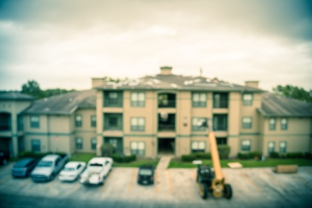 Filtered image blurry background roof replacement in progress at apartment building in USA Stok Fotoğraf