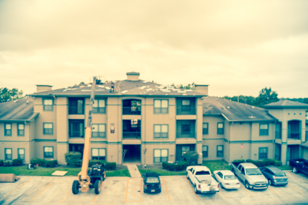 Filtered image blurry background roof replacement in progress at apartment building in USA