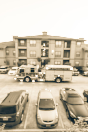 Filtered image blurry background aerial view of fire trucks at apartment building in America