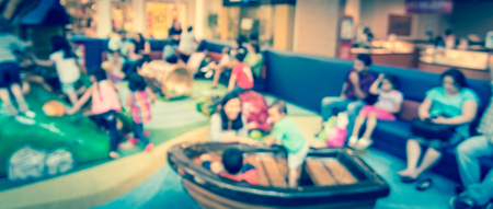 Panoramic view blurry background diverse kids playing at indoor soft playground inside shopping mall Stock Photo