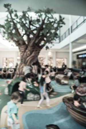 Filtered image blurry background diverse kids playing at indoor soft playground inside shopping mall