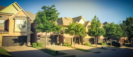New development neighborhood with row of attached houses and double garage doors
