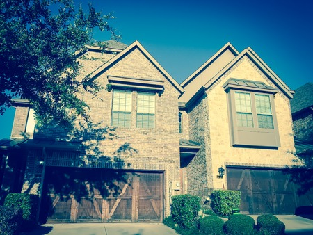 Filtered image front entrance of brand new house with wooden garage doors near Dallas, Texas