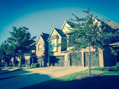 Filtered image front entrance of brand new house with wooden garage doors near Dallas, Texas 版權商用圖片