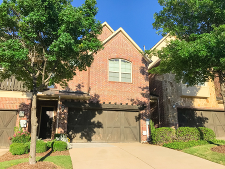 Front entrance of brand new house with wooden garage doors near Dallas, Texas