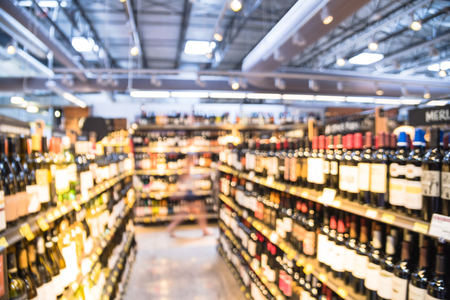 Blurry background customer shopping for wine bottles at American liquor store 免版税图像